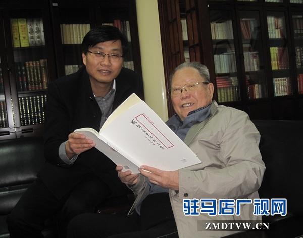 张全景部长在欣赏臧新义书法作品集.jpg