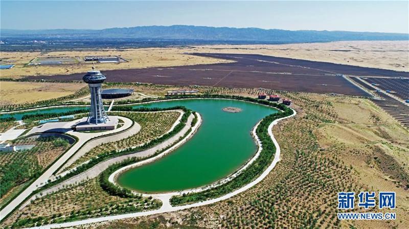 """地处宁夏中卫市腾格里沙漠边缘的中卫市沙漠光伏产业园,依托沙漠日照充足、地域广阔的优势,引进太阳能光伏组件制造、设备生产、光伏电站等企业,形成了""""硅料+硅片+光伏组件+光伏发电""""的全产业链发展规模,打造沙漠里的太阳能""""硅谷""""。新华社记者王鹏摄"""